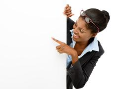 happy african american woman pointing at billboard sign white background - stock photo
