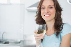 Pretty brunette having a glass of wine - stock photo