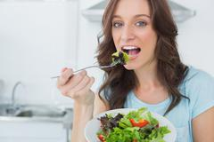 Stock Photo of Brunette eating healthy salad