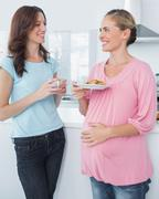 Stock Photo of Smiling pregnant woman holding cookies and her friend