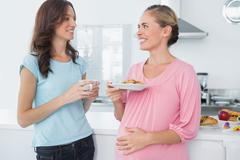 Stock Photo of Happy pregnant woman holding cookies and her friend