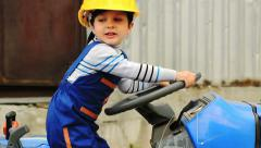 Portrait of Cute boy as a tractor driver turns the steering wheel - stock footage