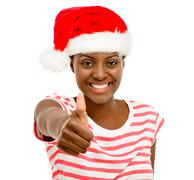 Cute african american girl fingers thumbs up sign wearing christmas hat isola Stock Photos