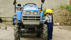 Portrait of Cute boy as a tractor driver turns the steering wheel Stock Footage
