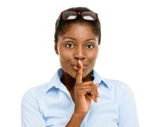 Stock Photo of happy african american business woman finger on lips isolated on white backgr
