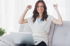 Cheering woman with laptop on her knees Stock Photos