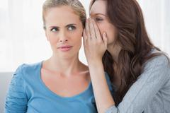 Blond woman hearing a secret from her friend - stock photo