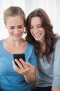Smiling friends reading message on their phone Stock Photos