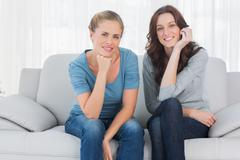 Pretty women posing while sitting on the couch - stock photo
