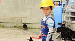Portrait of a cute boy in the role of worker stands near a tractor - stock footage