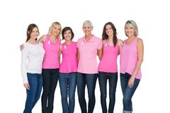 Smiling women wearing pink for breast cancer awareness - stock photo