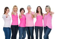 Positive women wearing pink for breast cancer posing Stock Photos
