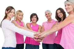 Cheerful women posing in circle holding hands looking at camera wearing pink for - stock photo