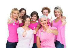 Positive women posing and wearing pink for breast cancer - stock photo