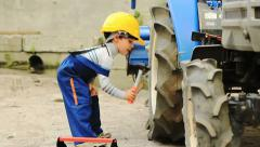 Cute little boy repairing a tractor wheel - stock footage