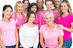 Voluntary pretty women posing and wearing pink for breast cancer - stock photo