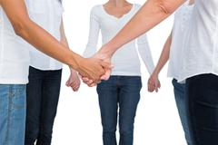 Women standing and holding hands in a circle - stock photo