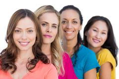 Smiling models in a line posing with colorful t shirts Stock Photos
