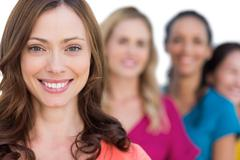 Smiling models in a line posing with focus on brunette Stock Photos