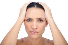 Young woman with headache touching her forehead - stock photo