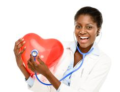 Happy african american trusted nurse holding red heart isolated on white back Stock Photos