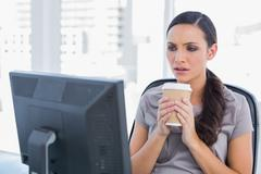 Unsmiling attractive businesswoman holding coffee - stock photo