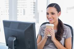 Stock Photo of Cheerful attractive woman holding coffee