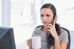 Frowning secretary answering phone Stock Photos