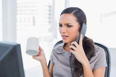 Irritated secretary answering phone and looking at computer screen - stock photo