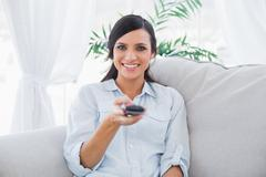 Stock Photo of Smiling attractive brunette holding remote