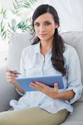 Stock Photo of Attractive brunette holding tablet pc and credit card