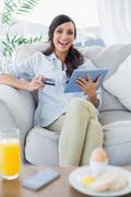 Cheerful gorgeous brunette buying online having breakfast - stock photo