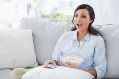 Astonished woman relaxing on the sofa eating popcorn Stock Photos