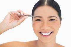 Stock Photo of Cheerful natural woman using tweezers for her eyebrow