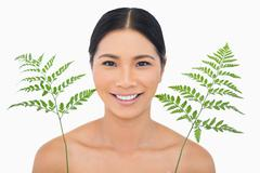 Stock Photo of Cheerful sensual dark haired model posing with fern