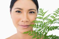 Stock Photo of Relaxed sensual model with fern caressing her face
