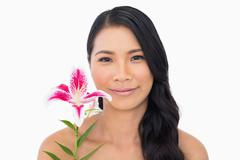 Peaceful natural brown haired model holding lily - stock photo