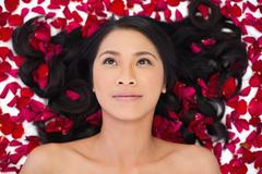 Pensive sensual dark haired model lying in rose petals Stock Photos
