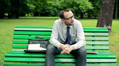 Young businessman sitting on bench in the park HD Stock Footage