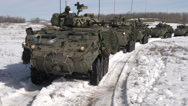 Stock Video Footage of military, moving line of LAV3 armoured fighting vehicles, rear view POV
