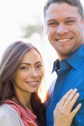 Happy couple standing outside - stock photo