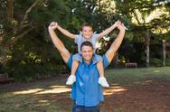 Stock Photo of Father holding his son on shoulders