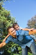 Stock Photo of Son lying on his fathers back