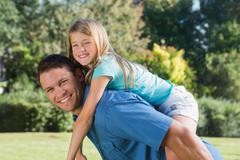 Daughter getting piggy back from dad - stock photo