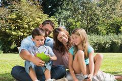 Happy family in a park with father and son inspecting leaf with magnifying glass Stock Photos