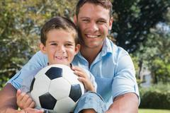 Happy dad and son with a football in a park - stock photo
