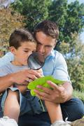 Dad and son inspecting leaf with a magnifying glass - stock photo