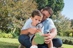 Cheerful dad and son inspecting leaf with a magnifying glass - stock photo