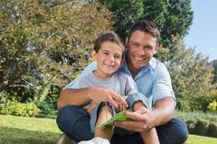 Smiling dad and son holding a leaf - stock photo