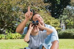 Dad and son looking at the sky with binoculars - stock photo